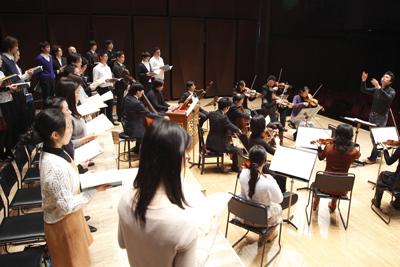合唱団と、指揮する渡辺祐介氏